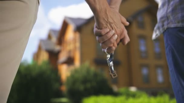 Elderly couple holding hands with house key