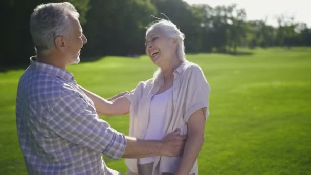 Atraktivní starší pár se smíchem na zeleném trávníku