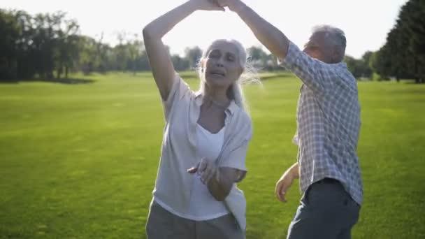 Pozitivní starší pár, tančí a zpívá na trávníku