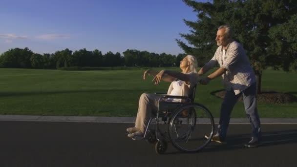 Uomo con la moglie in sedia a rotelle che gode allaperto