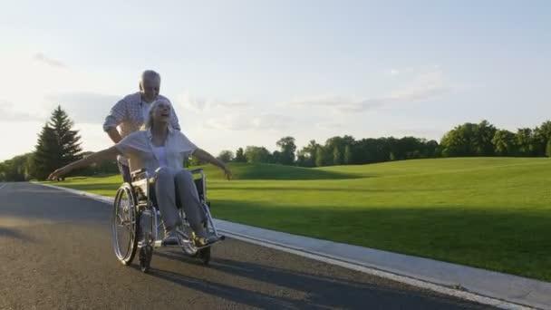 Coppia di pensionati, moglie sulla vita godendo di sedia a rotelle