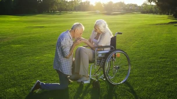 Manžel něžně líbat ruce manželku na invalidní vozík