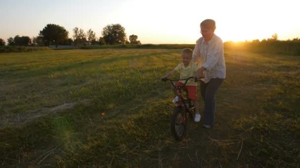 Grandmother teaching grandson to ride a bike
