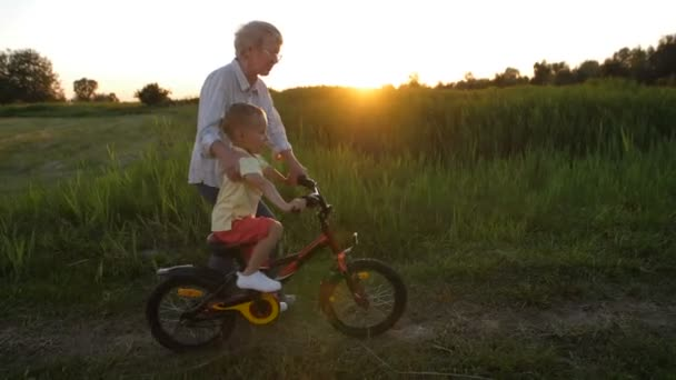 Toddler boy riding bicycle with grandmothers help