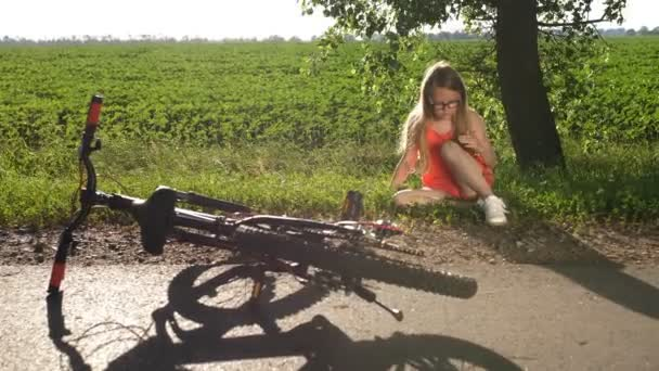 Teenage girl sitting on road after bicycle crash