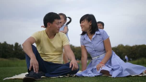Cute asian siblings embracing parents in nature