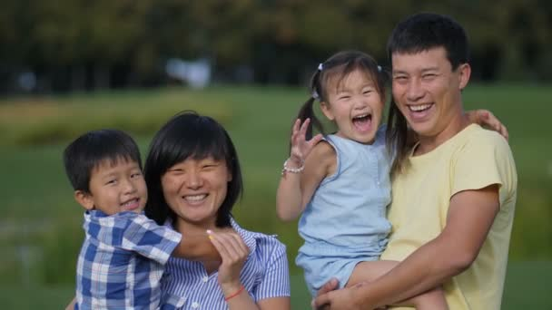 Excited asian family of four laughing in park