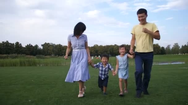 Asian family holding hands and running in park