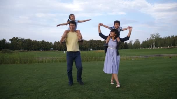 Cheerful asian parents carrying kids on shoulders