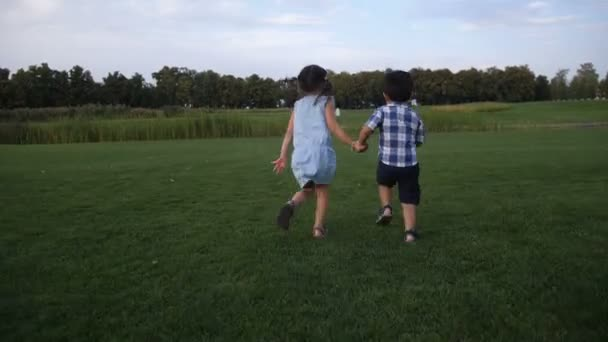 Rear view of two siblings running in summer park