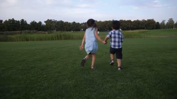 Zadní pohled ze dvou sourozenců v letním parku
