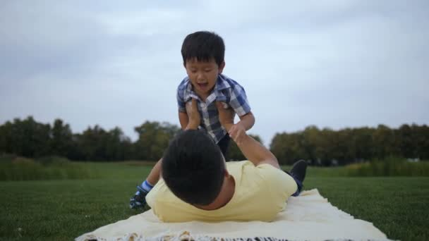 Loving father playing with his adorable asian son