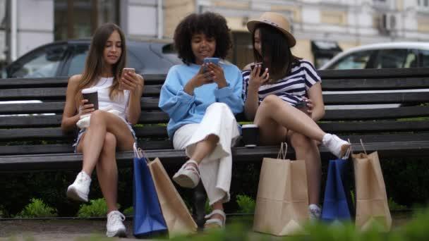 Dívky s telefony sedí na lavičce po nakupování