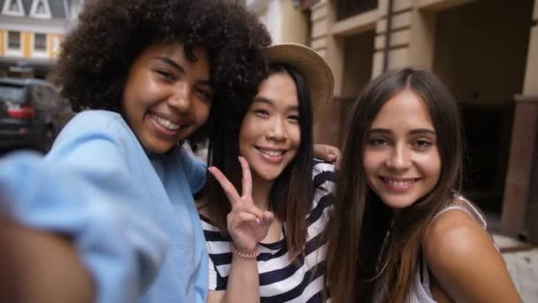 Cheerful multi ethnic girls taking selfie outdoors