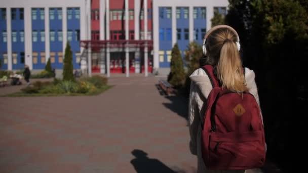 Roztomilá školačka pěšky směrem k budově školy