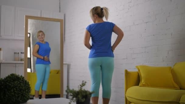 Vzrušená žena kontrolu její vzhled v zrcadle