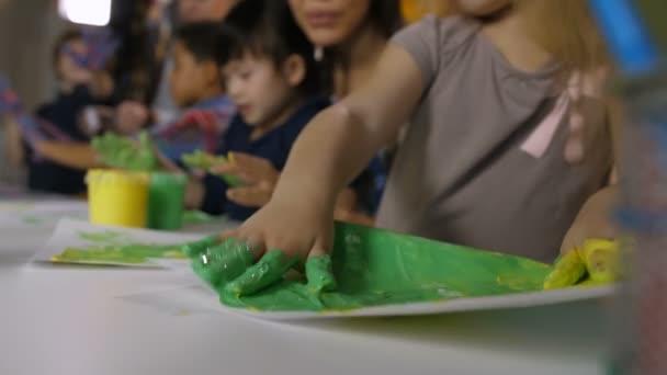 Closeup předškolní dívky ruce v pestré barvy vytvořit obrázek s ruční malování na uměleckou třídu ve školce s rozmazaný multikulturní učitele a děti udržet práce s obrazy pozadí