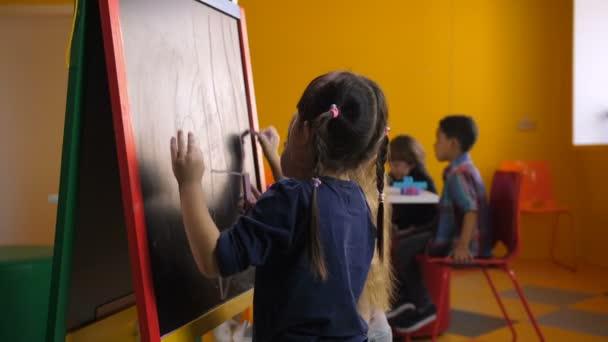 Vidám multi etnikai lányok támaszkodva chalkboard