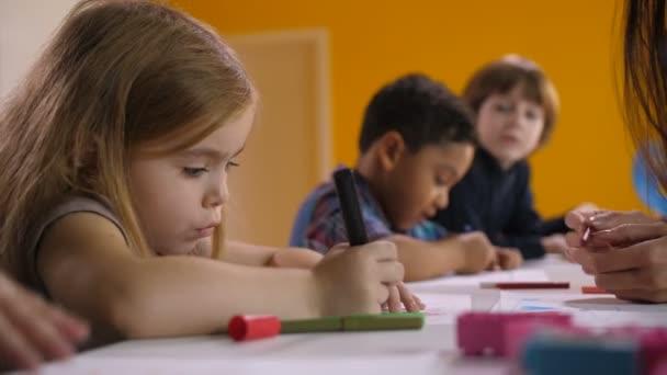 Roztomilá zabraný holčička kreslení na lekce umění