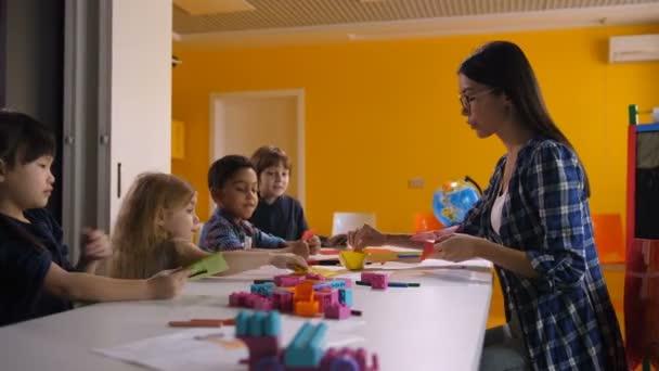 Učitelek výuky multikulturní rozmanité dětí dělat origami loď od barevný papír na uměleckou třídu ve školce. Předškolní pedagog vysvětlující děti jak udělat origami loď na lekci
