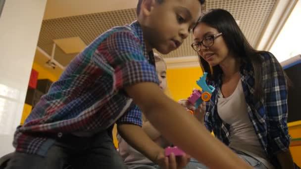 Učitel s rozmanité děti hrají s didaktické hračky