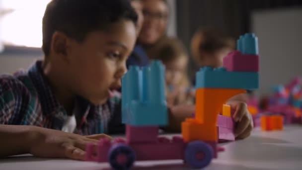 Mnohonárodnostní děti hrají s konstruktor ve třídě