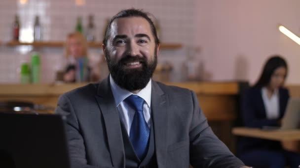 Portrait of smiling bearded businessman indoors