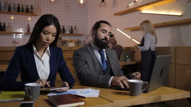 Podnikatelé, pracující na digitálních zařízeních v kavárně