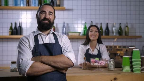 Positive Coffeeshop-Mitarbeiter in Schürzen lächeln