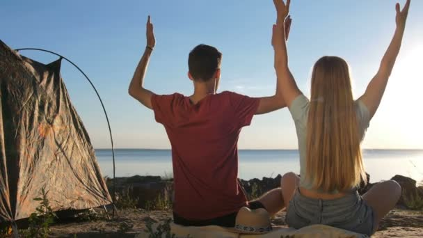 Rear view of couple meditating on shore near tent