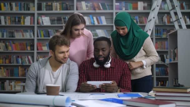 Studenti s tablet pc zkoumá v knihovně