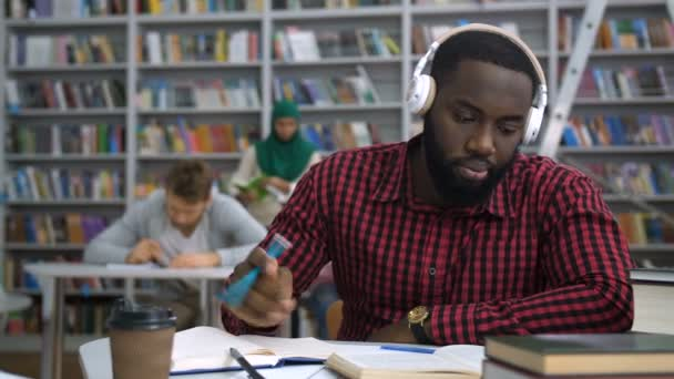 Dark-skinned student studying with book in library