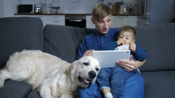 Dad and son with dog watching cartoons on touchpad