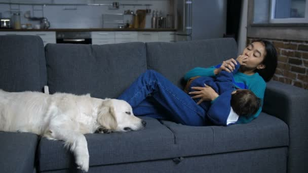 Hindu mom and infant relaxing on sofa with dog