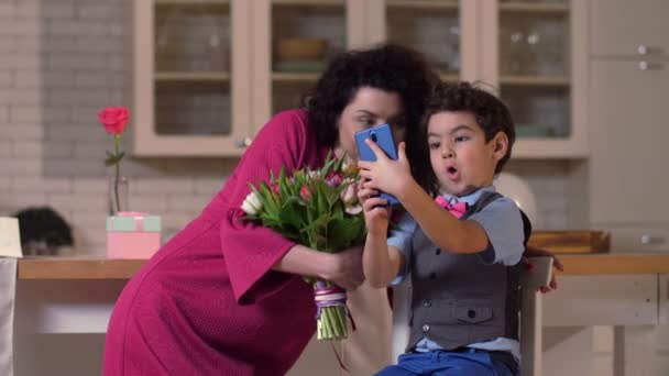Son with mom taking funny selfie photos on phone