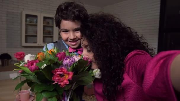 Joyful mom taking selfie with son holding flowers