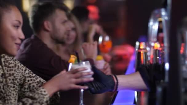 Junge Frau flirtet mit Barkeeper im Nachtclub