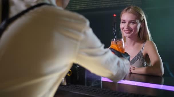 Schöne Frau, die vom Barkeeper im Club cocktail