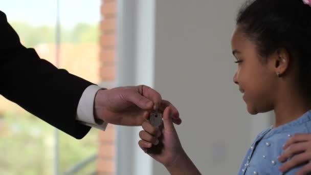Realtor handing keys to cute little homeowner girl