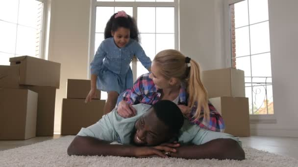 Happy family hugging while making stack on carpet