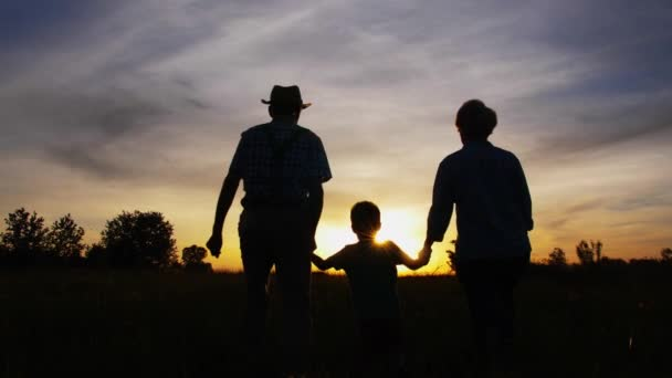 Grandparents and little grandson walking at sunset