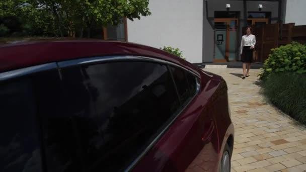 Geschäftsfrau geht von Haus aus auf Auto zu