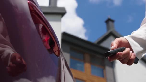 Female hand unlocking car door with key fob