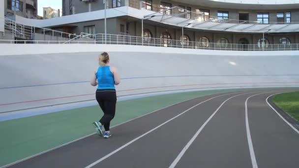 Il sovrappeso delle donne che si fa jogging sulla pista dello stadio cittadino