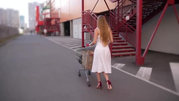 Donna bionda che trasporta carrello della spesa al parcheggio
