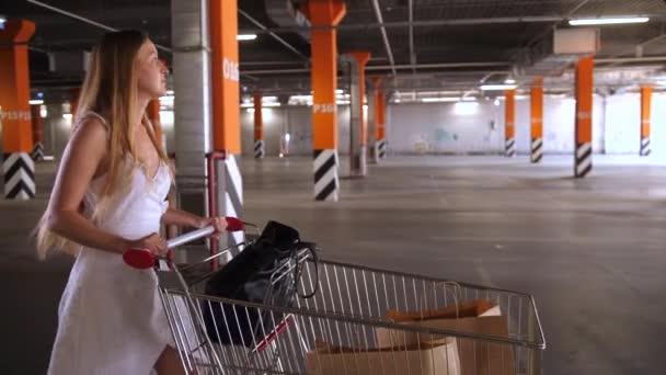 Krásná žena s nákupním vozíkem na parkovišti
