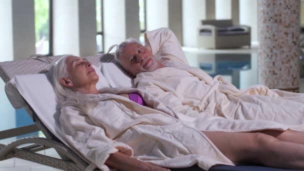 Stárnoucí pár v relaxaci na lehátka podle bazénu v hotelu