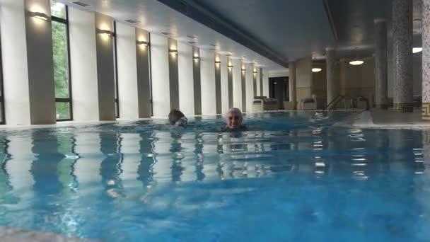 Aktivní stárnoucí dvojice plavání v hotelovém bazénu