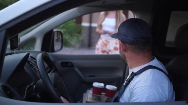Ženská klientka bere kávu od doručovatelky