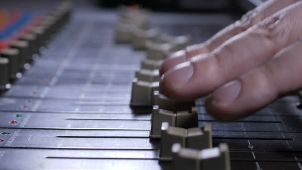 Faders sliding under fingers of record producer
